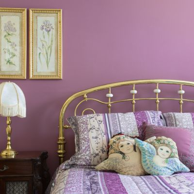 Lavender bedroom interior with brass furnishings and headboard