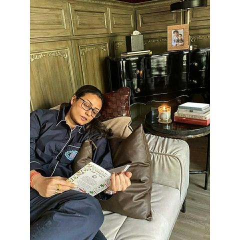 Namrata reading book at her house